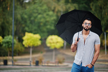 Fashionable Tall Arab Beard Man Wear On Shirt, Jeans And Sunglasses With Umbrella Posed At Rain On Park Square.