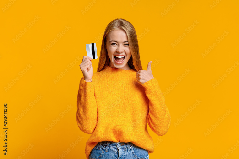 Fototapeta Carefree young girl showing thumb up, excited about upcoming shopping