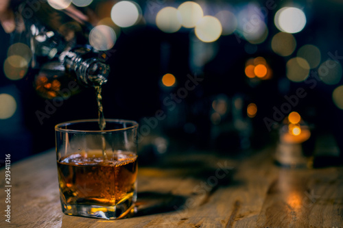 glass of whiskey and ice on wooden table Canvas Print