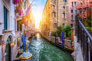 Uski kanal s mostom u Veneciji, Italija. Arhitektura i znamenitost Venecije. Ugodan gradski krajolik Venecije.