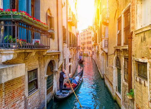 Narrow canal with gondola and bridge in Venice, Italy. Architecture and landmark of Venice. Cozy cityscape of Venice. - 293413758