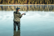 A Male Fisherman On The Lake Is Standing In The Water And Fishing For A Fishing Rod. Fishing Hobby Vacation Concept. Copy Space.