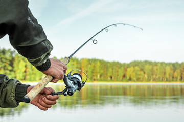 Hands of a man in a Urp plan hold a fishing rod, a fisherman catches fish at dawn. Fishing hobby vacation concept. Copy space.