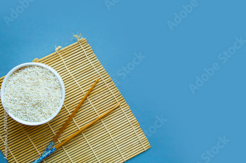 Photo Dry white rice in a bowl and chinese chopsticks