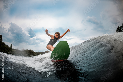 Girl wakesurfer glides smoothly on a board