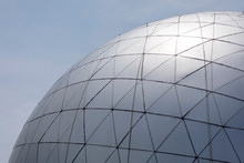 Space Age Modern Silver Dome Structure With Hexagonal And Triangular Patterns Against A Blue Sky