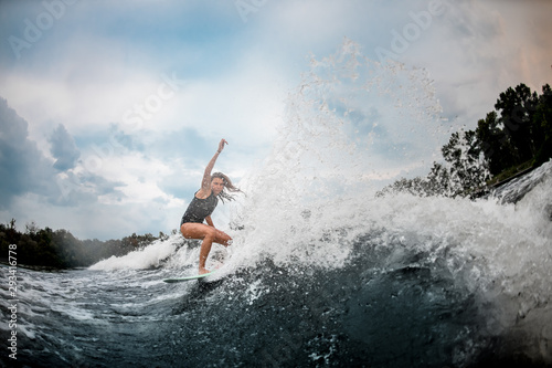 Girl wakesurfer slides smoothly on a board