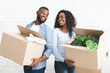 canvas print picture - Young couple holding cardboard boxes, smiling to each other