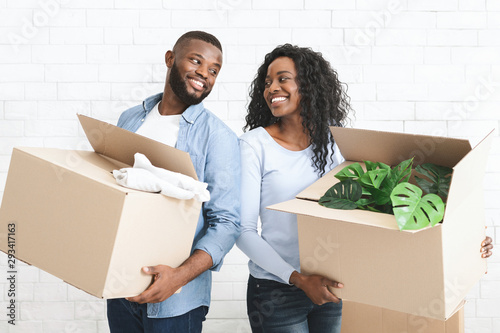 Young couple holding cardboard boxes, smiling to each other - 293417163