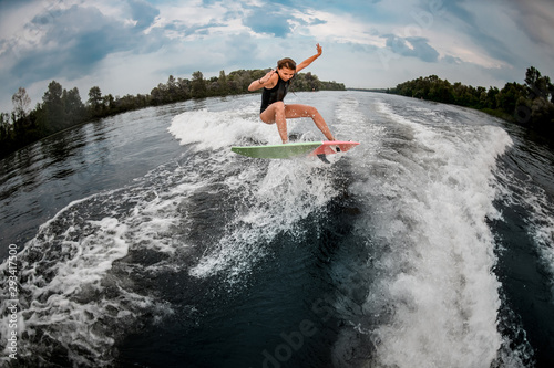 Girl wakesurfer jumps with the surf board