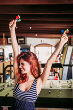 Happy Young Woman Holding Darts And Cheering In A Sports Bar