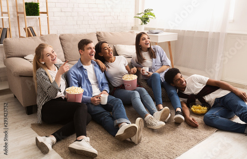 Fotografie, Obraz Happy friends watching comedy film and eating popcorn
