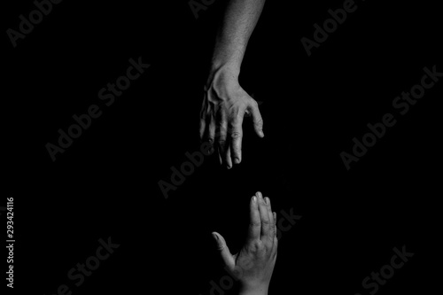 Photo Helping Hand, Hand reaching, trying to pull up and rescue, black background, cop