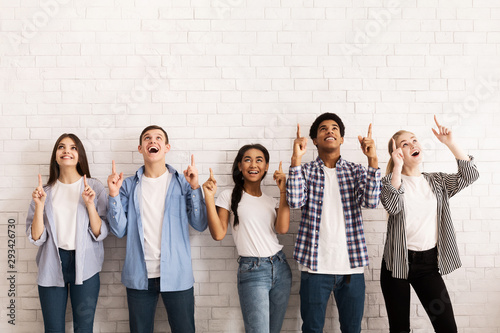 Teen friends pointing up on free space over white wall Wallpaper Mural