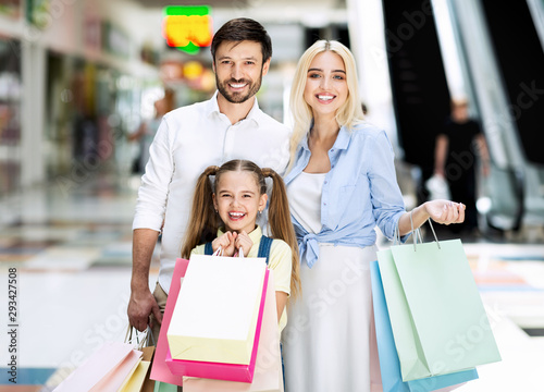 Valokuva  Family Smiling At Camera Standing Holding Shopping Bags In Mall