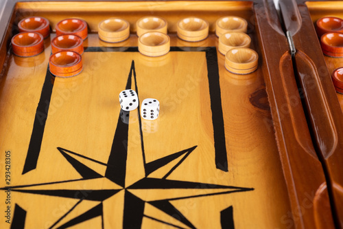Dice and checkers on a wooden backgammon board. Wallpaper Mural