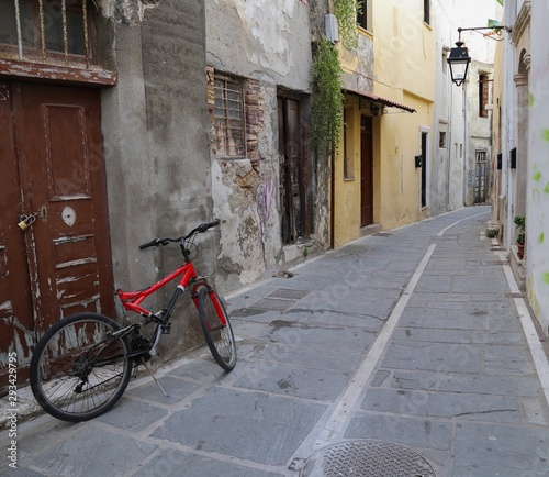 Fototapety, obrazy: The Red Bicycle in an old alleyway