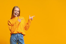 Cheerful Teenage Girl Pointing At Copy Space On Orange Background