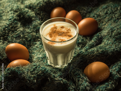 Eggnog. Traditional Christmas drink made from raw chicken eggs and milk with cinnamon in glass.