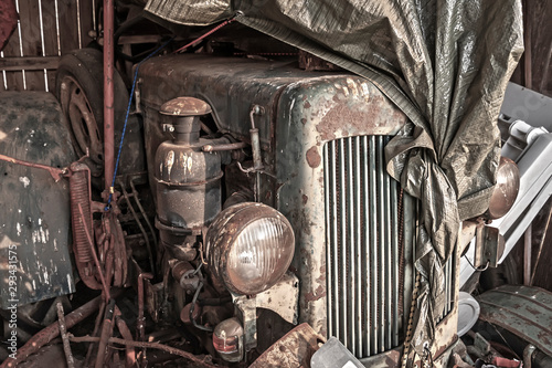 Old rusty tractor in a barn under a plastic wrap. Fototapet