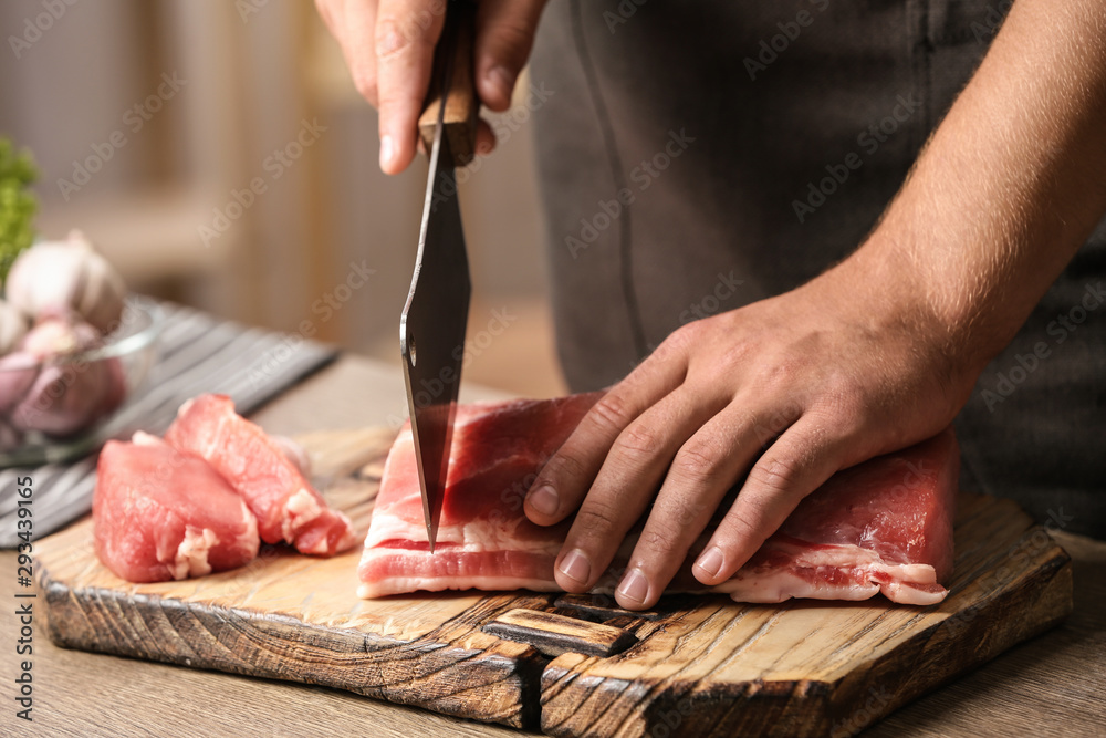 Fototapeta Man cutting fresh raw meat on table in kitchen, closeup