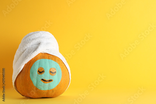 Fotografía  Pumpkin with facial mask and towel on yellow background, copy space