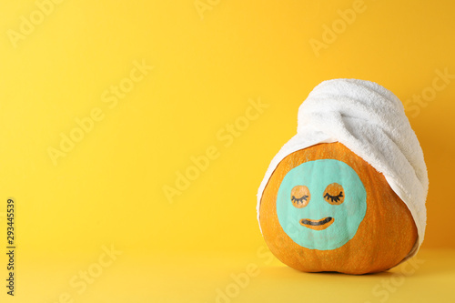 Recess Fitting Spa Pumpkin with facial mask and towel on yellow background, copy space