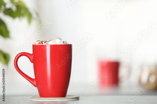 Cup of tasty cocoa with marshmallows on table indoors. Space for text