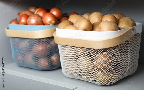 Fototapeta Baskets with potatoes and onions on shelf. Orderly storage obraz