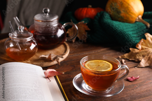 Cup of hot drink and book on wooden table. Cozy autumn atmosphere