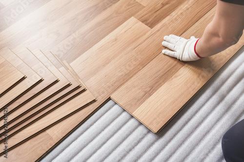 Obraz Installing laminated floor, detail on man hand in white glove fitting wooden tile, over white foam base layer - fototapety do salonu