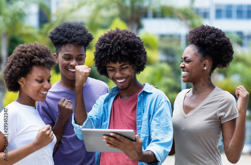 Fotografie, Obraz  Cheering group of african american university students with digital tablet