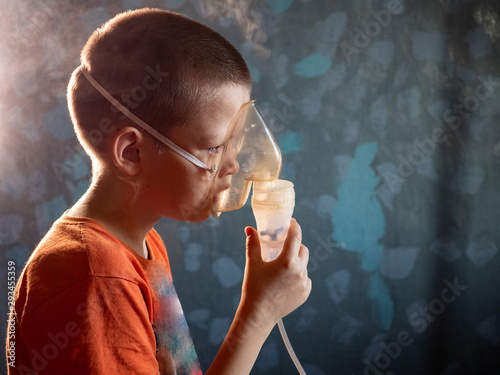 Fotografía  Caucasian blond boy inhales vapors containing medications to stop coughing