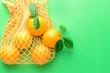 Leinwandbild Motiv Bag with ripe oranges on color background