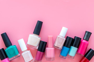 Choose nail polish. Polish bottels on pink background top view copy space