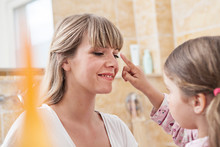 Germany, North Rhine Westphalia, Cologne, Daughter Applying Cream To Mother In Bathroom, Smiling