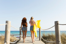 Rear View Of Young Women With Yellow Airbed And Sunshade Walking To The Beach