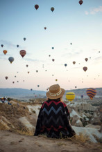 Young Woman And Hot Air Balloons In The Evening, Goreme, Cappadocia, Turkey
