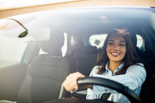 Beautiful Young Happy Smiling Woman Driving Her New Car At Sunset. Woman In Car. Close Up Portrait Of Pleasant Looking Female With Glad Positive Expression, Woman In Casual Wear  Driving A Car