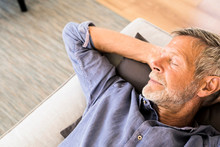 Senior Man Lying On Couch At Home Taking A Nap