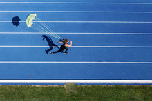 Top View Of Female, Runner With Parachute On Tartan Track