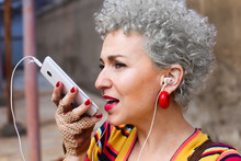 Portrait Of Pierced Mature, Woman With Grey Curly Hair Using Earphones And Cell Phone