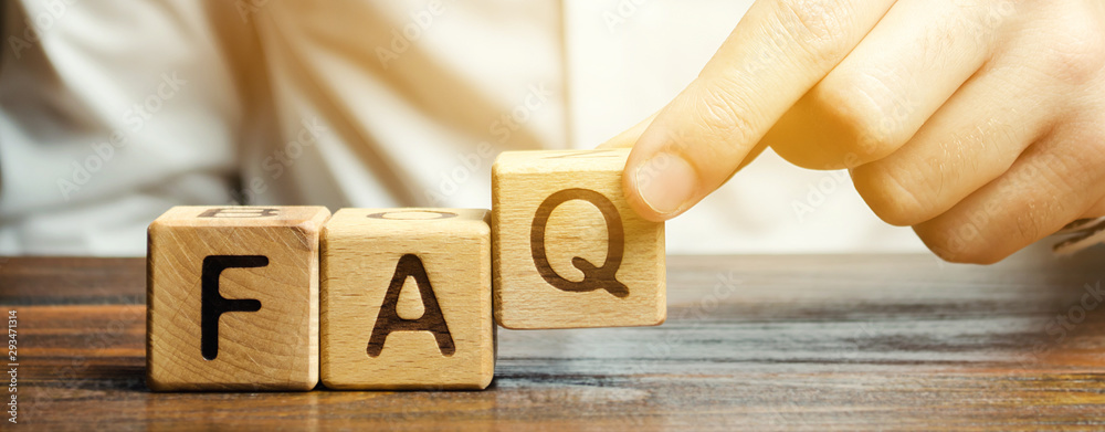 Fototapeta Businessman puts wooden blocks with the word FAQ (frequently asked questions). Collection of frequently asked questions on any topic and answers to them. Instructions and rules on Internet sites