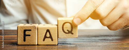 Fototapeta Businessman puts wooden blocks with the word FAQ (frequently asked questions). Collection of frequently asked questions on any topic and answers to them. Instructions and rules on Internet sites obraz
