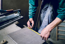 Close Up On Construction Worker Craftsman Using Tool For Cutting Ceramic Tiles For Laying Installation To The Bathroom Making Measurement Marks Using Measuring Tape And Pen