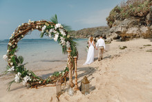 Happy Groom And Bride Walking On Whie Sand Beach  Under The Arch Decorated With Flowers In Boho Style. .Wedding Couple Just Married At The Beach, Bali. Wedding Ceremony