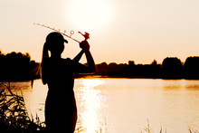 Silhouette Of A Woman At Sunset With A Fishing Rod Near The Pond.