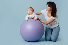 Happy Mother Doing Exercises With Her Infant Child Baby On Purple Yoga Ball
