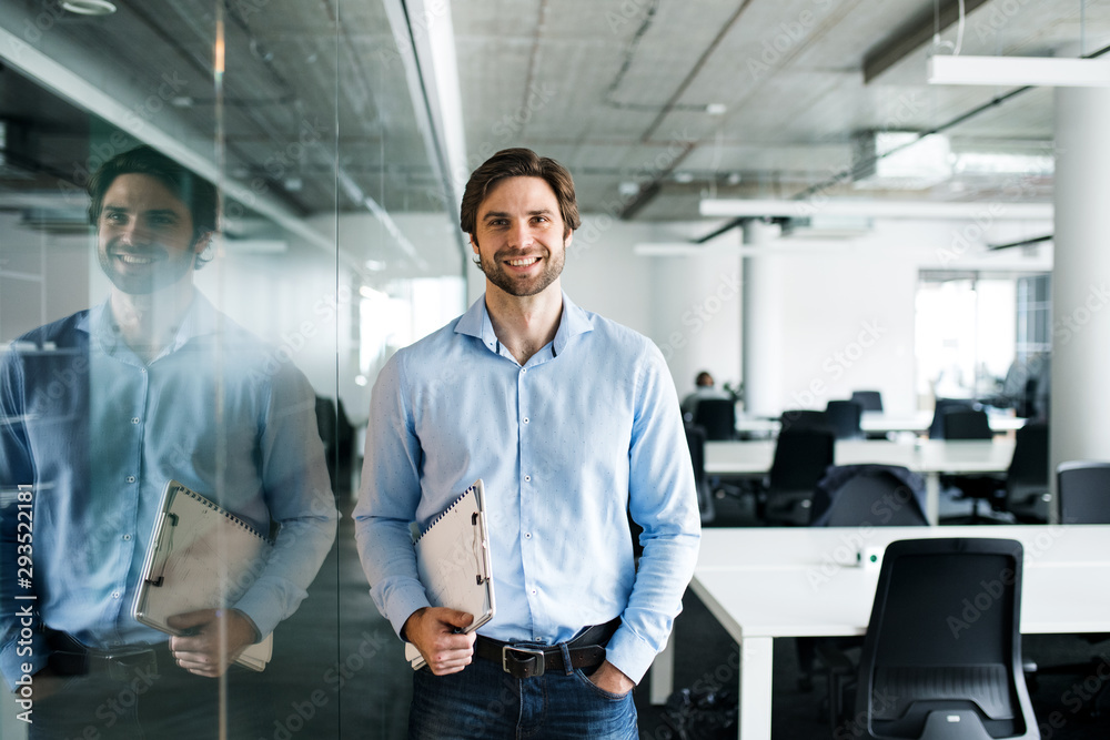 Fototapeta Portrait of young businessman standing in an office, looking at camera.