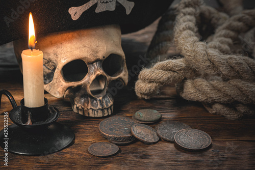 Fototapeta Human skull in a pirate hat, old coins, mooring rope and burning candle on brown wooden desk background